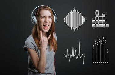 Excited teenager showing a rock sign while listening to music in headphones