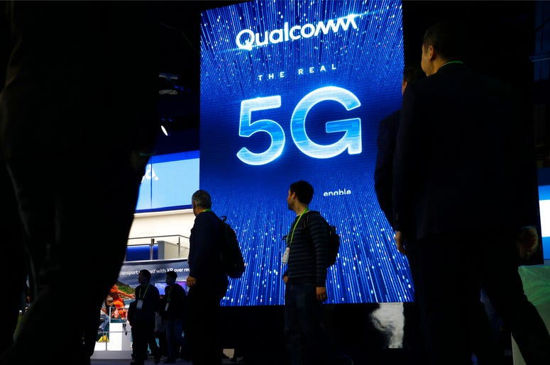 In this Jan. 9, 2019, file photo a sign advertises 5G at the Qualcomm booth at CES International in Las Vegas. Qualcomm and Apple drove declines in technology stocks on Wednesday, May 22. Qualcomm plunged following a federal judge's ruling against the chi