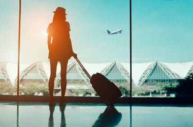 Silhouette woman travel with luggage looking without window at airport terminal international or girl teenager traveling in vacation
