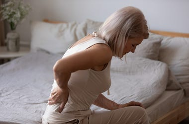 Woman on edge of bed rubbing back in pain