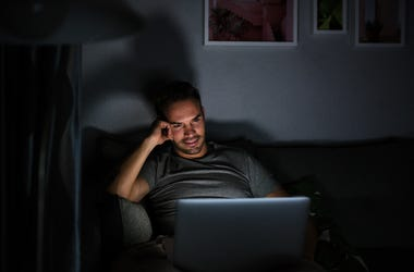 Man in dark room binge watching TV