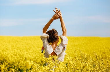 woman in the middle of a field of yellow flowers