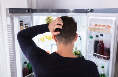Man looking into fridge perplexed