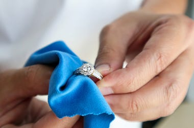 person cleaning a ring with a soft towel