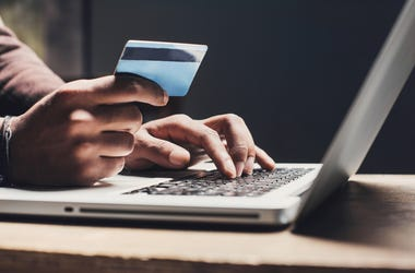 hand holding credit card at computer for shopping