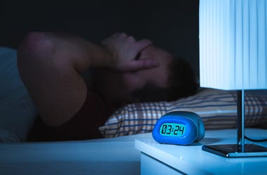 Man awake with clock reading 3am