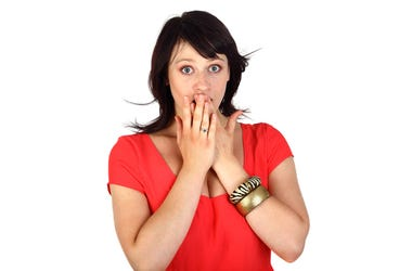 Woman with surprised look & hands over mouth