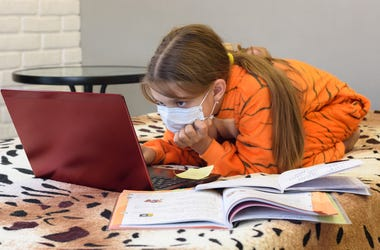 Girl doing schoolwork on her bed in pajamas