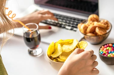 Woman Eating Junk Food at Computer