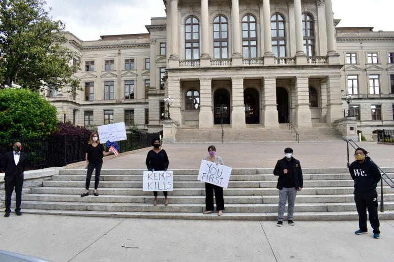 Protesters participate in mock funeral outside GA State Capitol as the stay at home order is scheduled to expire at 11:59pm