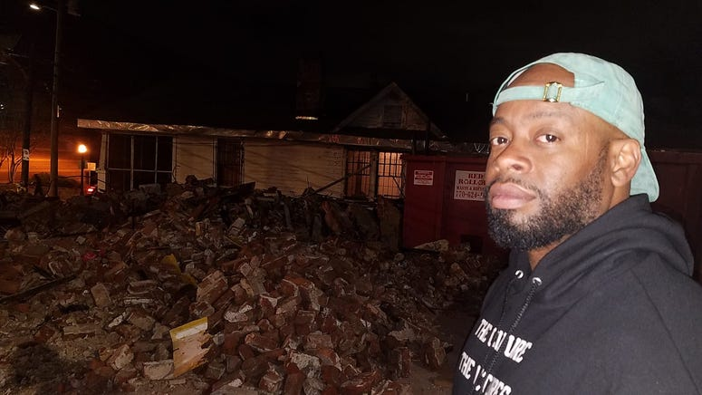 Muralist Fabian Williams looks at the remains of the building that featured his Kaepernick mural