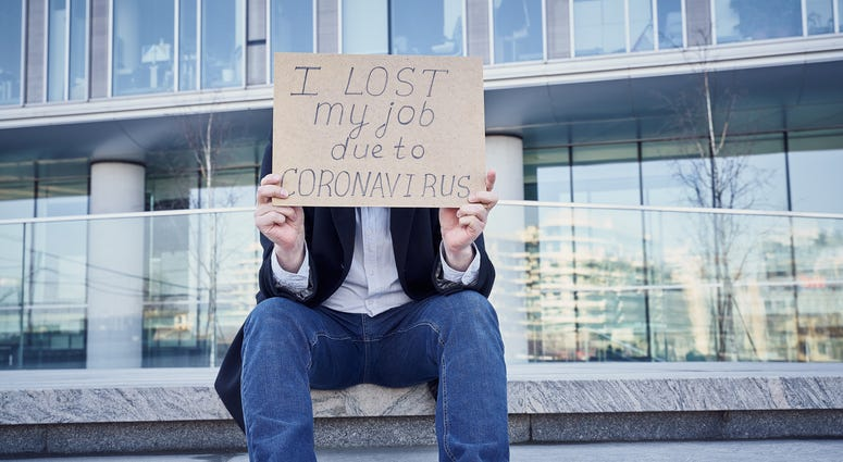 "A man holds sign ""I lost my job because of coronavirus."" as he sits Male sitting on stairs of building at his  former place of work in the business center."