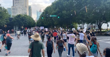 """Protesters chanted """"Black Lives Matter Too"""" as they walked down Peachtree Street in Atlanta Tuesday."""