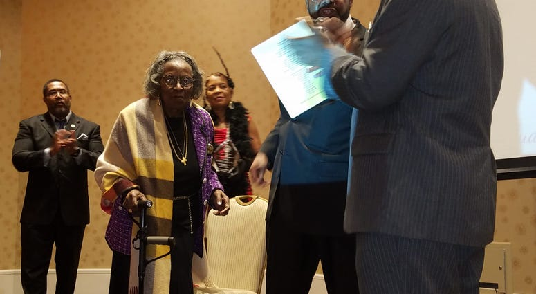 Mrs. Juanita Abernathy walks across the stage during an NAACP event earlier this year