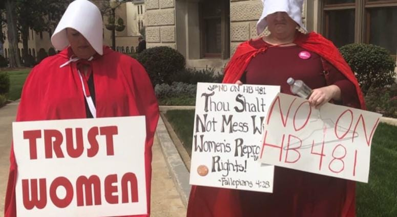"""Dressed as characters from the fictional tv show and book """"The Handmaids Tail"""" (about a totalitarian society) protestors have been assembling at the GA Capitol"""