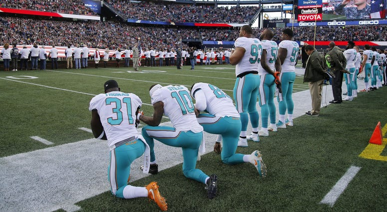 Dolphins players kneeling