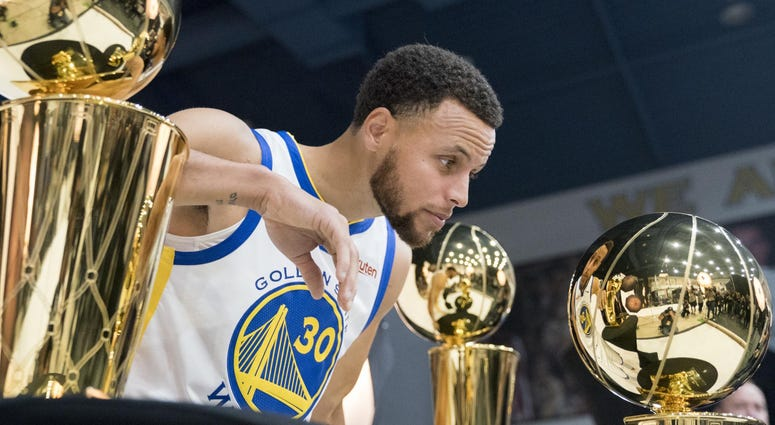 Stephen Curry of the Golden State Warriors poses with the NBA trophy.