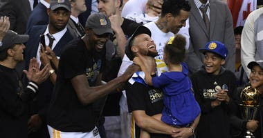 Golden State Warriors forward Kevin Durant (35) and guard Stephen Curry (30) celebrate after game five of the 2017 NBA Finals against the Cleveland Cavaliers at Oracle Arena.
