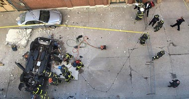 Indianapolis firefighters work on a vehicle that plunged off of the fourth floor of a downtown parking garage Wednesday morning