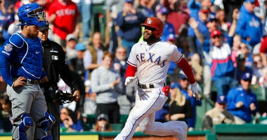 Texas Rangers' Delino DeShields, right, crosses home plate with Chicago Cubs catcher Victor Caratini, left, looking on after hitting a grand slam during the fourth inning of a baseball game in Arlington, Texas, Sunday, March 31, 2019.