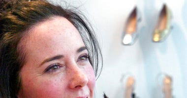 n this May 13, 2004 file photo, designer Kate Spade poses with shoes from her next collection in New York. Law enforcement officials say Tuesday, June 5, 2018, that New York fashion designer Kate Spade has been found dead in her apartment in an apparent s
