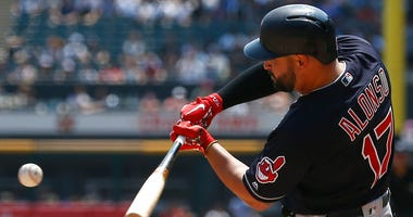 Cleveland Indians' Yonder Alonso hits an RBI single against the Chicago White Sox during the first inning of a baseball game Sunday, Aug. 12, 2018, in Chicago. (AP Photo/Jim Young)