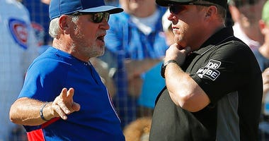 Chicago Cubs manager Joe Maddon, left, speaks to third base umpire Bruce Dreckman about a call on a play during the fourth inning of a baseball game against the Cincinnati Reds, Sunday, Sept. 16, 2018, in Chicago. (AP Photo/Jim Young)