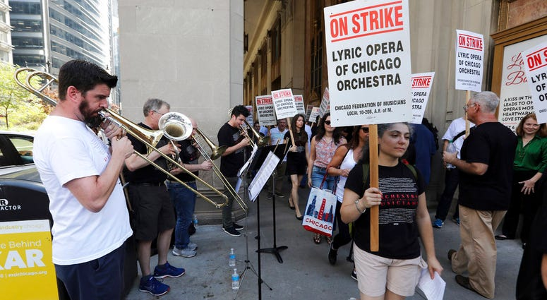 Jeremy Mueller, left, and other striking Lyric Opera musicians perform as their colleagues picket outside The Civic Opera House in Chicago on Tuesday, Oct. 9, 2018. (Terrence Antonio James/Chicago Tribune via AP)