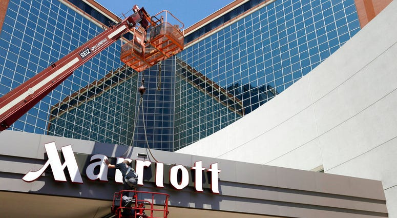 In this Tuesday, April 30, 2013, file photo, a man works on a new Marriott sign in front of the former Peabody Hotel in Little Rock, Ark. Marriott says the information of up to 500 million guests at its Starwood hotels has been compromised. It said Friday