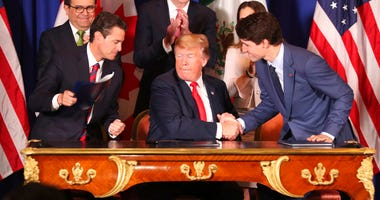 President Donald Trump, center, shakes hands with Canada's Prime Minister Justin Trudeau as Mexico's President Enrique Pena Nieto looks on after they signed a new United States-Mexico-Canada Agreement that is replacing the NAFTA trade deal, during a cerem