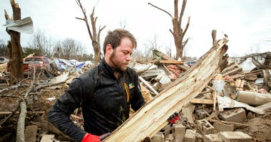 Steven Tirpak cleans debris from the remains of his two-story home in Taylorville, Ill., Sunday, Dec. 2, 2018. Tirpak and his infant were not home when the storm struck. The National Weather Service says multiple tornadoes touched down in central Illinois
