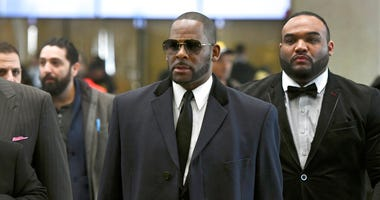 Musician R. Kelly, center, arrives at the Leighton Criminal Court building for a hearing in Chicago.