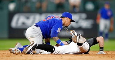 Chicago Cubs shortstop Javier Baez, left, tags out Colorado Rockies' Ryan McMahon as he slides into second base while trying to stretch his RBI-single into a double in the eighth inning of a baseball game, Monday, June 10, 2019, in Denver.