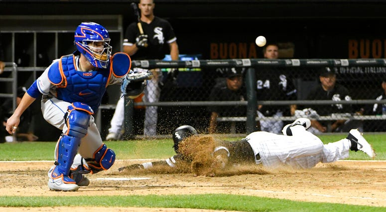 Chicago White Sox's Ryan Goins, right, scores as New York Mets catcher Tomas Nido waits for the throw during the ninth inning of a baseball game, Tuesday, July 30, 2019, in Chicago.
