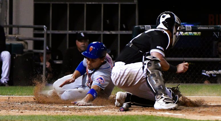 New York Mets' Michael Conforto, left, scores past Chicago White Sox catcher James McCann during the sixth inning of a baseball game Wednesday, July 31, 2019, in Chicago.