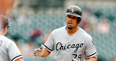 Chicago White Sox's Jose Abreu is greeted by third base coach Nick Capra after a solo home run during the first inning of the first game of a baseball doubleheader against the Detroit Tigers, Tuesday, Aug. 6, 2019, in Detroit.
