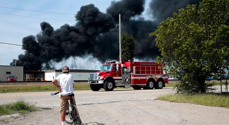 A resident watches as a firetruck arrives in downtown Dupo, Ill. to help fight a tanker fire from a derailed train on Tuesday, Sept. 10. 2019.