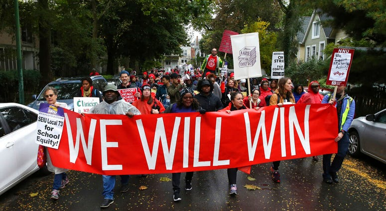 """Dozens of Chicago Teachers Union members and supporters march through the streets of Chicago's Hyde Park neighborhood during the """"Nurse in Every School"""" Solidarity March for Justice on Monday, Oct. 21, 2019."""