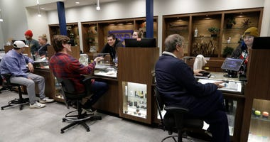 In this Thursday, Dec. 26, 2019 photo, registered medical marijuana patients talk with staff members at the Rise cannabis store in Mundelein, Ill. Starting Jan. 1, 2020, Illinois will join Michigan as the only Midwestern states broadly allowing the sale a