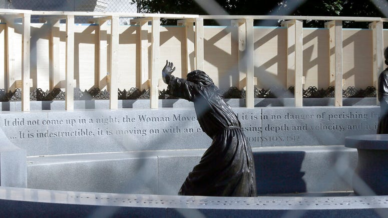 The statue of pioneer woman Laura Ingles is shown behind the fencing put up around the Virginia Women's Memorial on Capitol Square in Richmond, Va., Friday, Jan. 17, 2020.