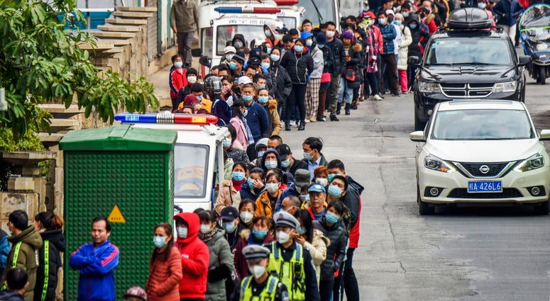 In this Jan. 29, 2020, file photo, people line up to buy face masks from a medical supply company in Nanning in southern China's Guangxi Zhuang Autonomous Region