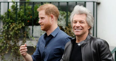 Britain's Prince Harry, the Duke of Sussex, left, smiles while walking along with musician Jon Bon Jovi as he leaves Abbey Road Studios in London, Friday, Feb. 28, 2020.