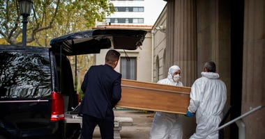 Undertakers carry a coffin for a burial at a Barcelona cemetery during the coronavirus outbreak, Spain, Friday, March 27, 2020.