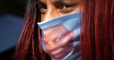 A woman wears a face covering with the likeness of shooting victim Ahmaud Arbery printed on it during a rally to protest Arbery's killing Friday, May 8, 2020, in Brunswick Ga.