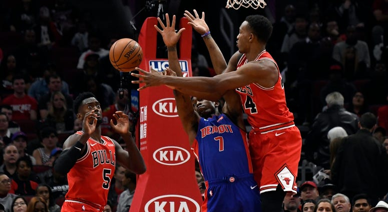 Bulls center Wendell Carter Jr. (34) passes the ball to forward Bobby Portis (5) as Pistons forward Stanley Johnson (7) defends.