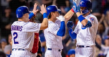 Kris Bryant gets high-fives after hitting a grand slam in the Chicago Cubs' win over the St. Louis Cardinals on May 5, 2019.