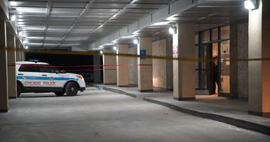 Chicago police tape off the entry to an apartment building where a woman stabbed her father, left a baby in a bathtub, then jumped from the 11th floor with another Jan. 2, 2019.
