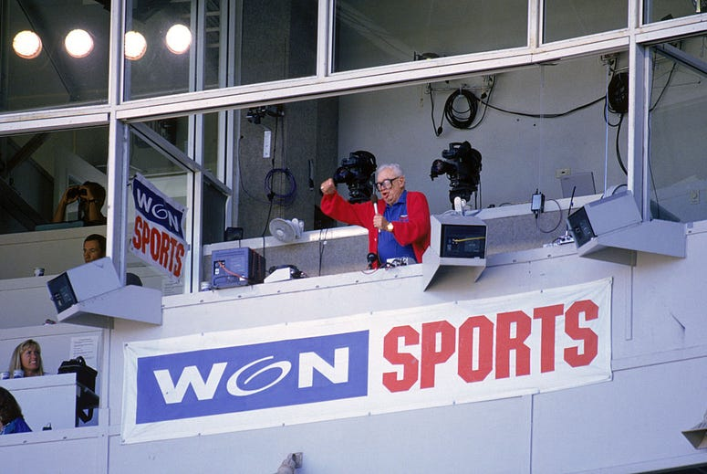 Chicago Cubs baseball announcer and Baseball Hall of Fame inductee Harry Caray conducts fans singing 'Take Me Out to the Ball Game' from his television booth during the seventh inning stretch in a game against the Colorado Rockies at Wrigley Field