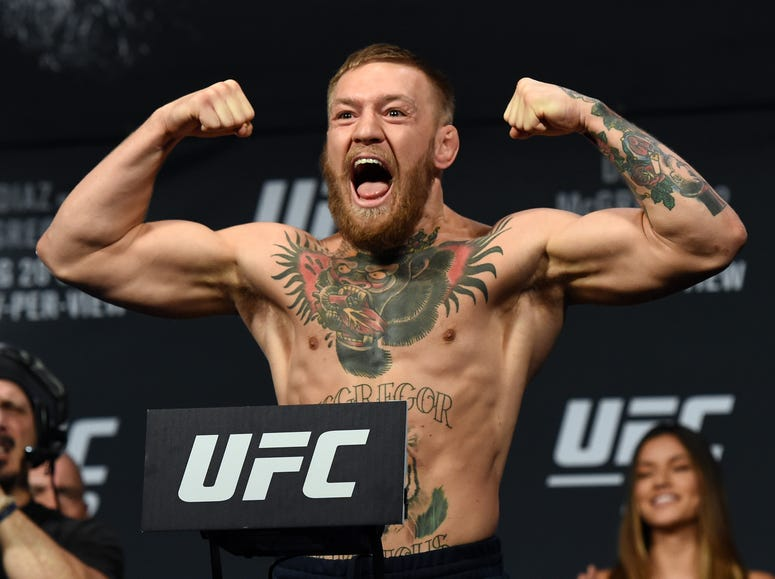 UFC featherweight champion Conor McGregor poses on the scale during his weigh-in for UFC 202 at MGM Grand Conference Center on August 19, 2016 in Las Vegas, Nevada.