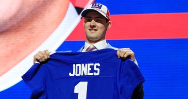 Daniel Jones poses with his New York Giants jersey on stage at the 2019 NFL Draft.